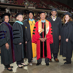 College president and board members in graduation robes
