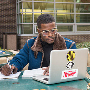 student working at laptop computer while sitting outside on a sunny day