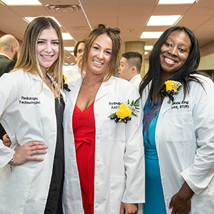3 nursing students standing together smiling during their graduation