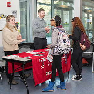 2 students talking to admission specialist from a visiting college at a dual admissions information table