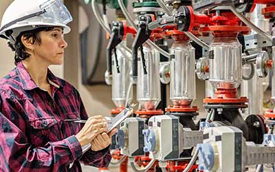 Women overseeing the operation of pipe valves