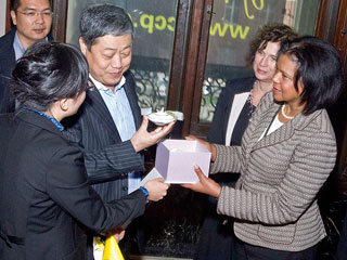 Administrators at an event with one presenting a small gift to another