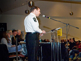 Presentation froma member of the police. uniformed presenter facing a crowd of people, presenting from a podium.