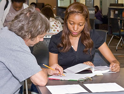 student sitting at table workign with a counselor with papers on the table