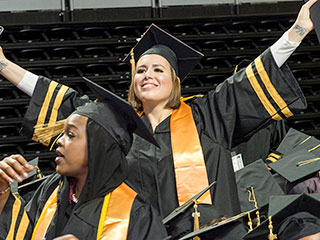 graduate excited with arms raised up