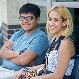 2 students sitting outside looking at camera
