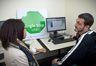 A singles stop counselor working with a student in front of a computer.