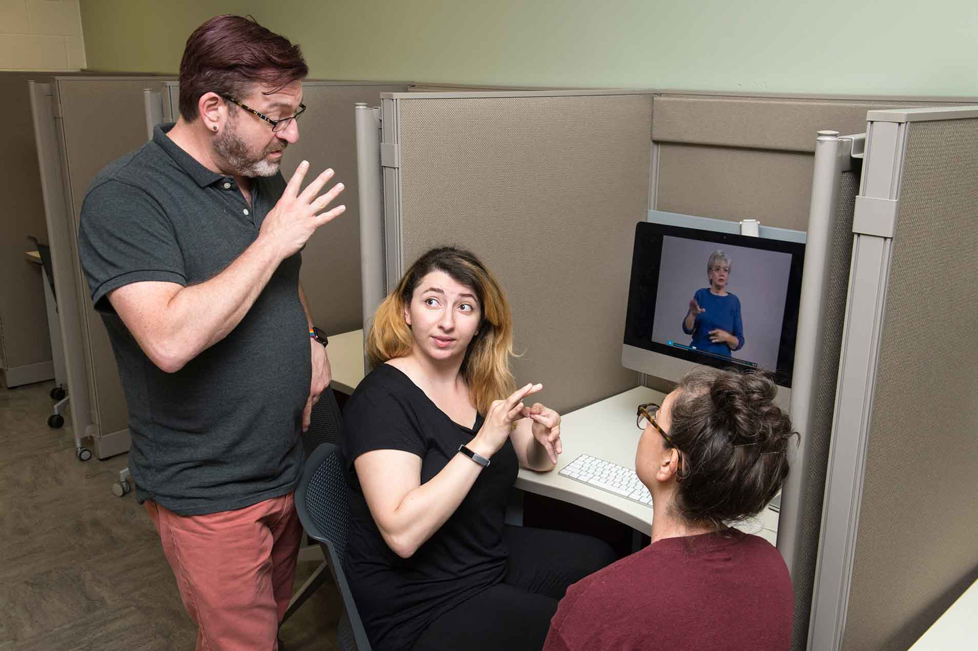 Three people practicing American sign language with the help of video instruction.