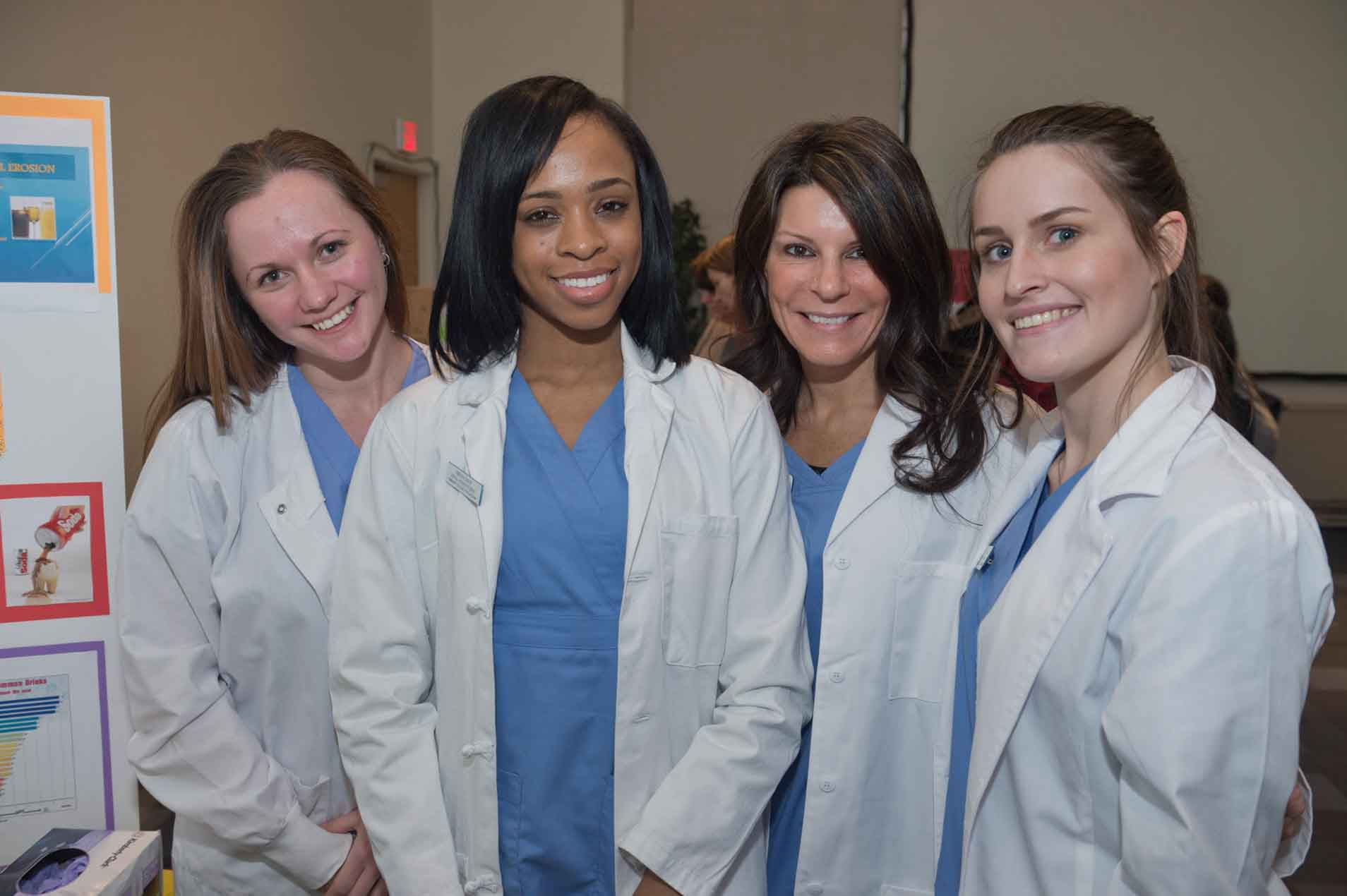 Four women in blue scrubs and white medical coats.