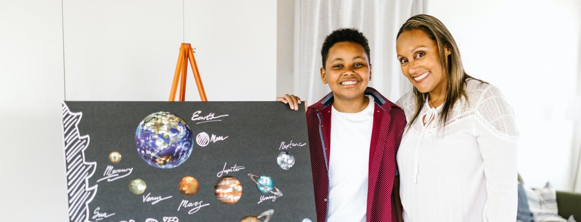 Teacher and student smiling as student shows poster he made