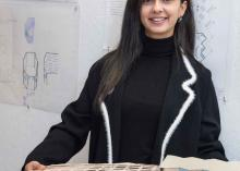 Student holding architectural design model in CCP class.