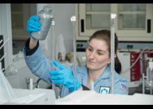 A science student pouring liquid in a container in a CCP lab.