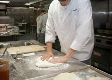 Student kneading dough in CCP kitchen.