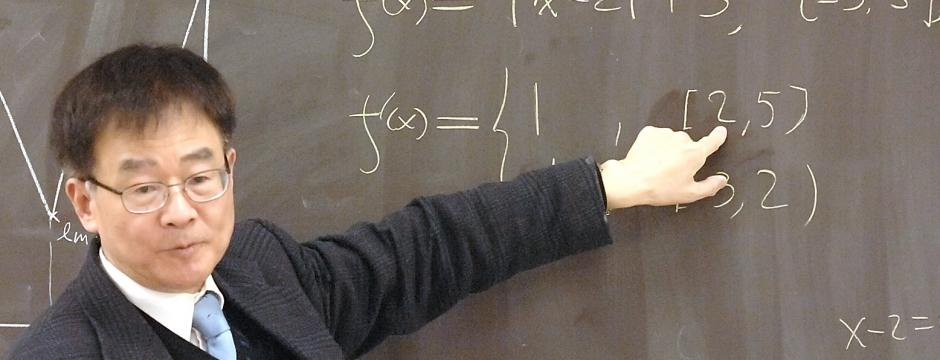Professor teaching mathematics on chalkboard at Community College of Philadelphia.