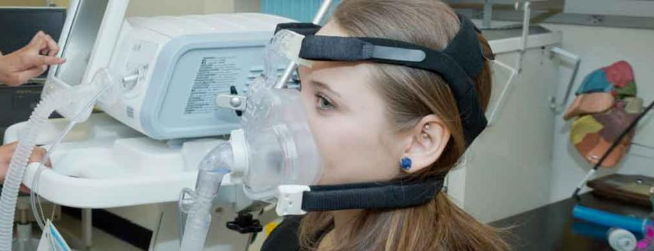 CCP student in respiratory care testing machine.