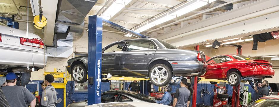 Students working on automobiles in garage at CCP.