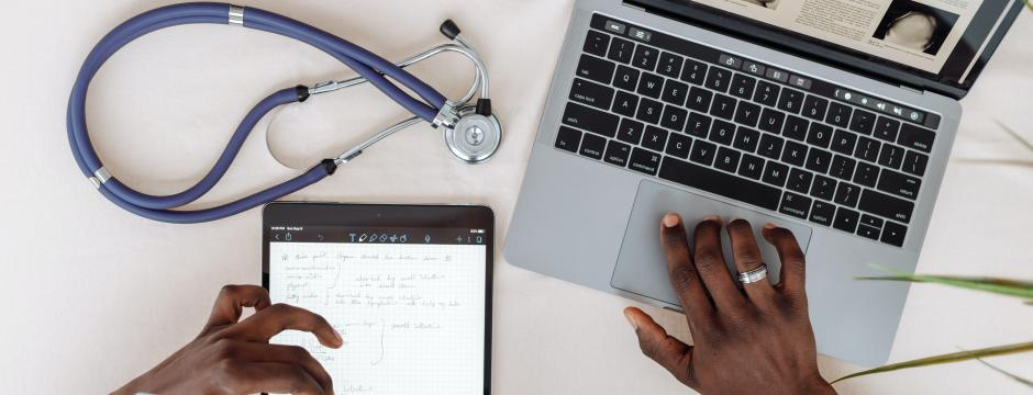 Hands working on a laptop and iPad with a stethoscope in the background